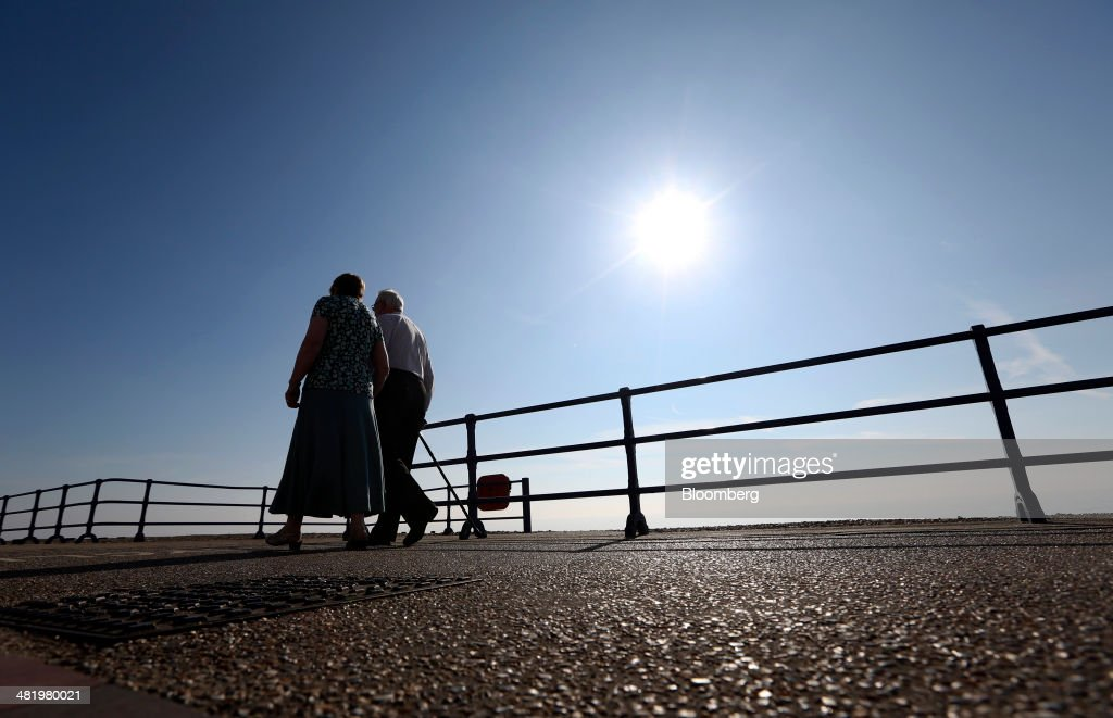 Pedestrians walk along the beachfront promenade in Eastbourne, U.K., on Tuesday, April 1, 2014. Pensioners and savers have seen returns on their money shrink since the financial crisis drove interest rates to a record low. Photographer: Chris Ratcliffe/Bloomberg via Getty Images