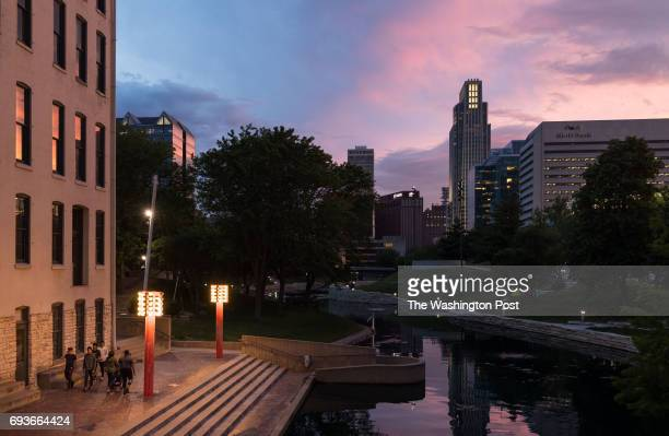 Pedestrians walk along the Gene Leahy Mall at sunset in Omaha Neb on May 31 2017