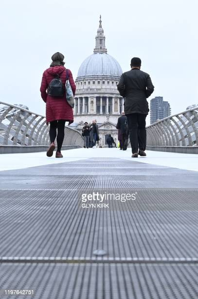 Pedestrians walk along the Millennium Footbridge toward St Paul's Cathedral across the River Thames in London on January 31 2020 on the day that the...