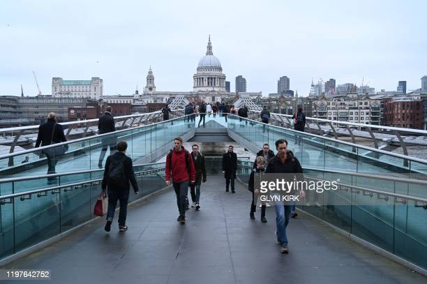 Pedestrians walk along the Millennium Footbridge with St Paul's Cathedral in the background across the River Thames in London on January 31, 2020 on...