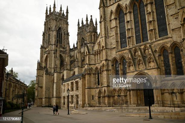 Pedestrians walk along the near-deserted street alongside York Minster in York, northern England on May 12, 2020. - Following an announcement by the...