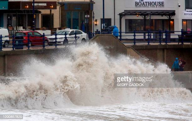 Pedestrians walk along the promenade as huge waves crash against the sea wall at Porthcawl, south Wales as Storm Dennis hits the country on February...
