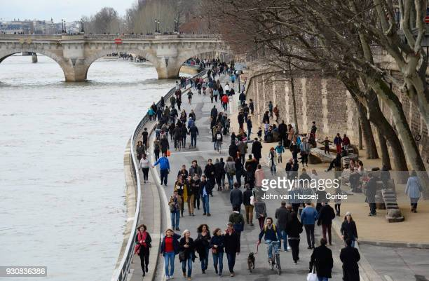 Pedestrians walk along the river Seine near the Pont Neuf on March 10 2018 in Paris France Pedestrians and cyclists assembled to support a carfree...