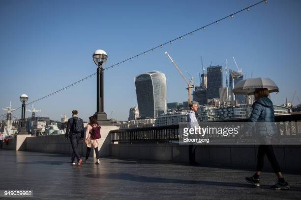 Pedestrians walk along the River Thames in view of 20 Fenchurch Street also known as the 'WalkieTalkie' in London UK on Friday April 20 2018 Foreign...