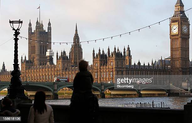 Pedestrians walk along the River Thames opposite the Houses of Parliament and Big Ben clocktower right in London UK on Friday Dec 21 2012 Britain's...