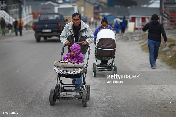 Pedestrians walk along the road on July 26, 2013 in Ilulissat, Greenland. As Greenlanders adapt to the changing climate and go on with their lives,...