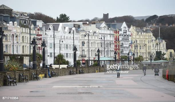 Pedestrians walk along the seafront promenade in Douglas on the Isle of Man an island in the Irish Sea off of the west coast England on November 8...