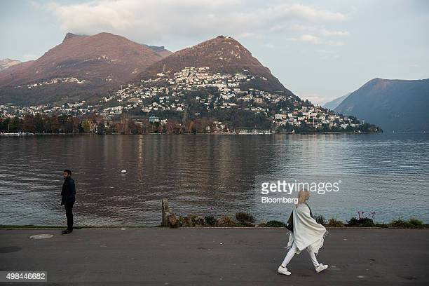 Pedestrians walk along the side of Lake Lugano as residential properties sit on a hillside in the distance in Lugano Switzerland on Friday Nov 20...