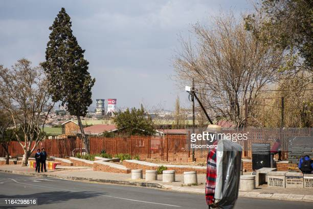 Pedestrians walk along the street as the cooling towers of the decommissioned Orlando Power Station stand in the distance in Kliptown, Soweto, South...
