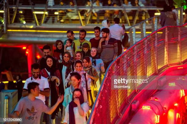 Pedestrians walk along the Tabiat pedestrian bridge at dusk in Tehran Iran on Saturday Aug 4 2018 Irans central bank acting on the eve of US...