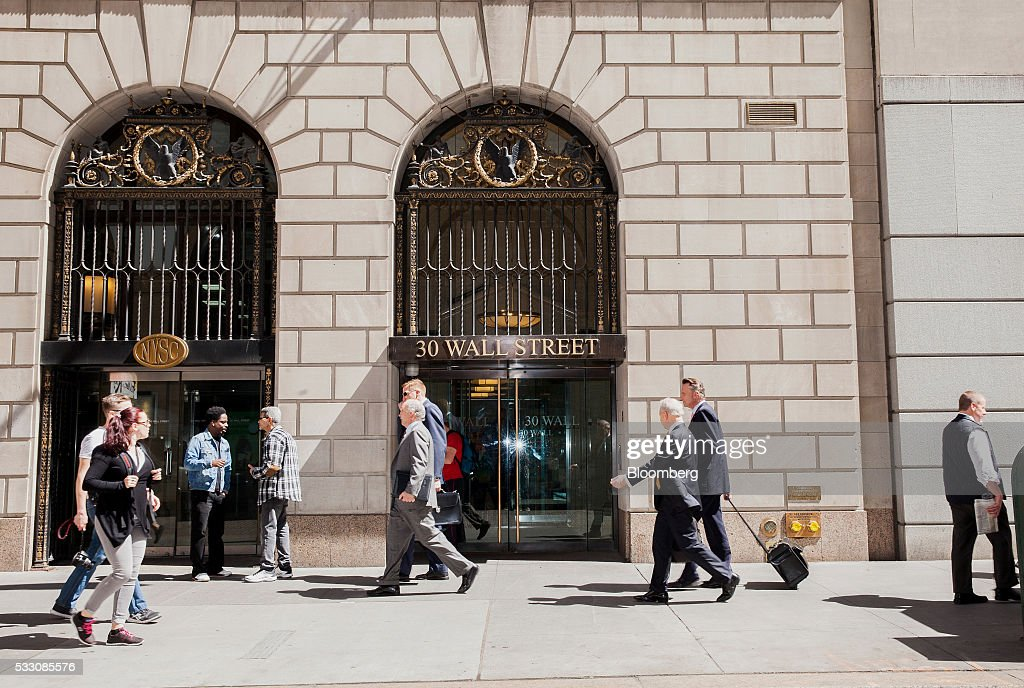 Pedestrians walk along Wall Street in New York, U.S., on Monday, April 18, 2016. U.S. stocks rose, with the S&P 500 bouncing from a seven-week low, led by a rally in technology shares amid ebbing anxiety over the potential for higher interest rates as early as next month. Photographer: David Williams/Bloomberg via Getty Images