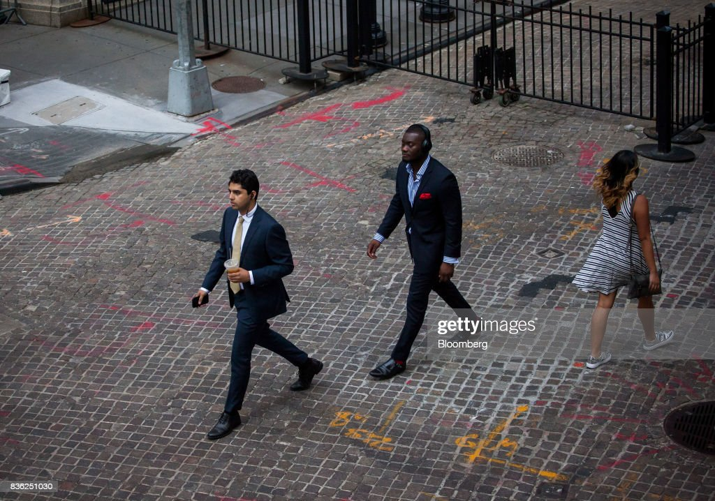 Pedestrians walk along Wall Street near the New York Stock Exchange (NYSE) in New York, U.S., on Monday, Aug. 21, 2017. U.S. stocks fluctuated after erasing early losses, while the dollar edged lower amidgrowing uneaseabout persistent low inflation and as investors await central bank speeches at Jackson Hole. Photographer: Michael Nagle/Bloomberg via Getty Images