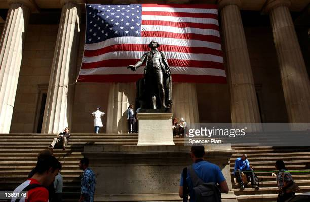 Pedestrians walk around the George Washington statue in front of Federal Hall September 5 2002 in New York City Congress will return to its 18th...