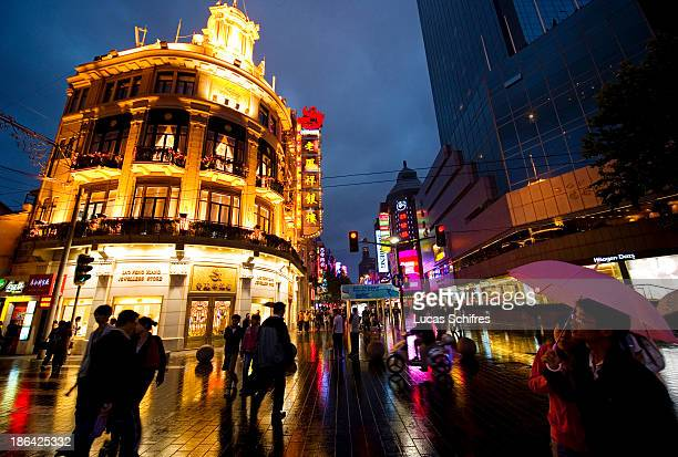 Pedestrians walk at dusk on Nanjing lu the busiest commercial street of Shanghai China on May 23 2011