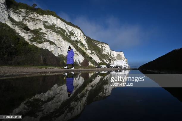 Pedestrians walk at St Margaret's Beach as The White Cliffs are reflected in a puddle in Dover on the south coast of England on December 31, 2020 the...