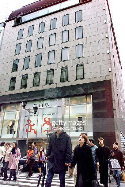 Pedestrians walk before a fashion store owned by Japan's troubled supermarket operator Daiei at Tokyo's Ginza fashion district 27 January 2002 Daiei...