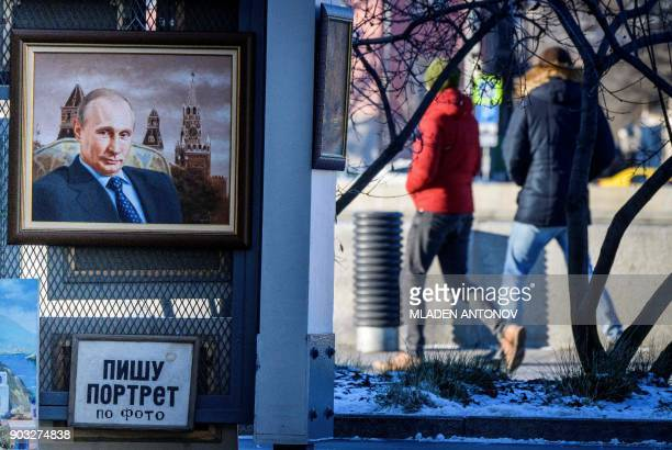 Pedestrians walk behind a portrait of Russian President Vladimir Putin for sale at an art market in Moscow on January 10 2018 Russia's presidential...