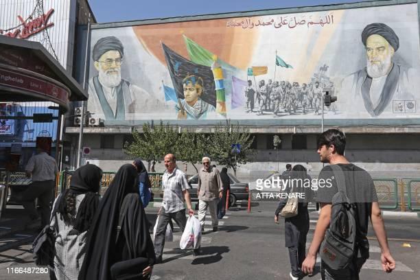 Pedestrians walk below a mural past a mural depicting former and current Supreme Leaders Ayatollah Ruhollah Khomeini and Ayatollah Ali Khamenei in...