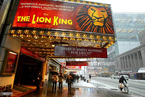 Pedestrians walk beneath a sign for the musical 'The Lion King' March 6 2003 in New York City About 325 Broadway theater musicians are set to go on...