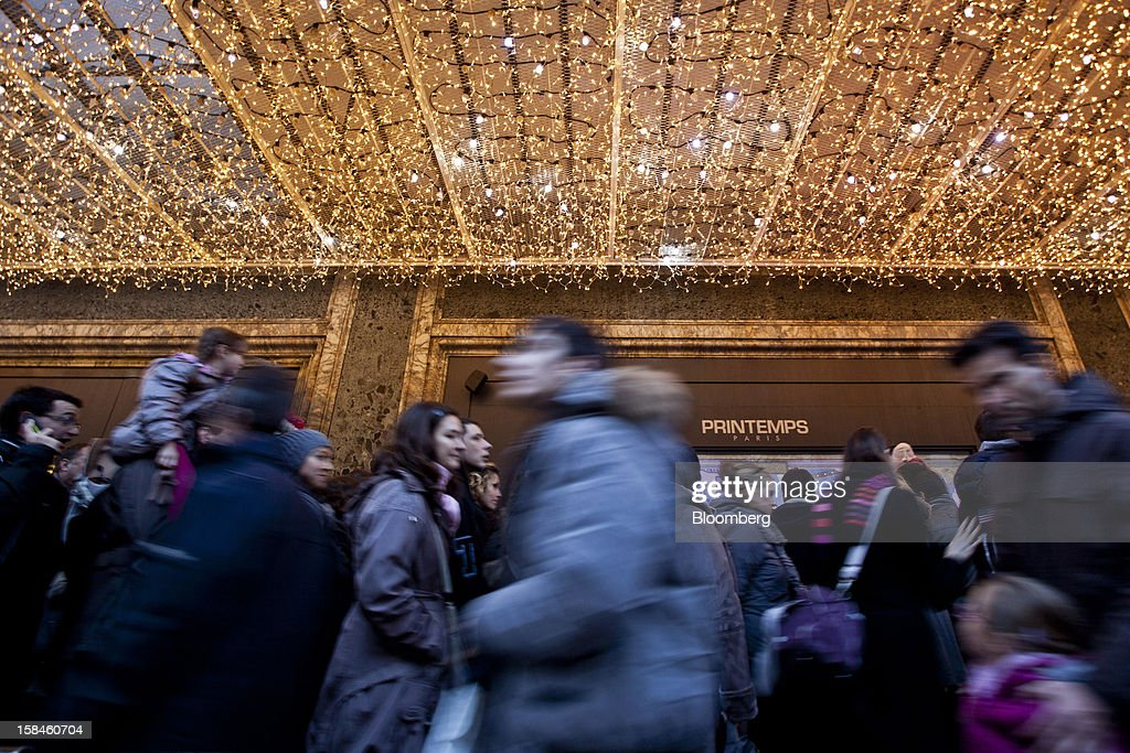 Pedestrians walk beneath an illuminated walkway outside a Printemps department store in Paris, France, on Saturday, Dec. 15, 2012. The French minister for energy and environment unveiled a proposal for lights in and outside shops, offices, and public buildings -- including the flagship Louis Vuitton store and the Lido cabaret house on Paris's Avenue des Champs Elysees -- to be turned off between 1 a.m. and 7 a.m. starting in July. Photographer: Balint Porneczi/Bloomberg via Getty Images