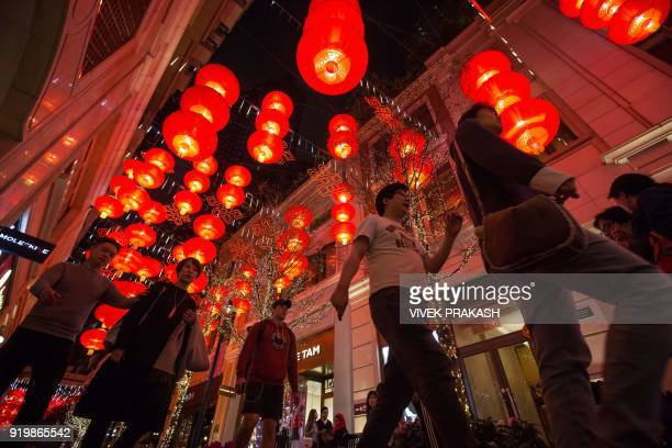 Pedestrians walk beneath red lanterns hung up over a street during Lunar New Year celebrations for the Year of the Dog in Hong Kong on February 18...