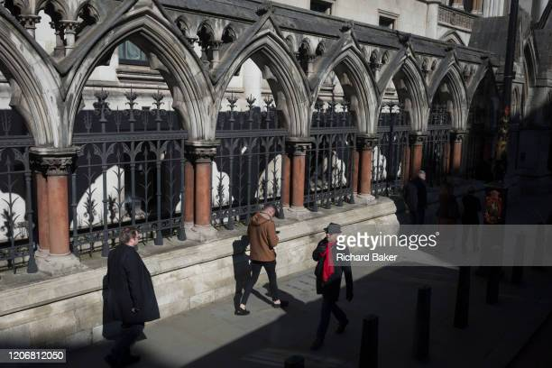 Pedestrians walk beneath the Gothic arches of the Royal Courts of Justice on the Strand, on 11th march 2020, in London, England. Designed by George...