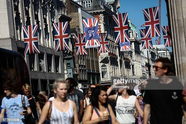 Pedestrians walk beneath Union Flags also known as Union Jacks suspended above Oxford Street in London UK on Tuesday July 19 2016 UK inflation...