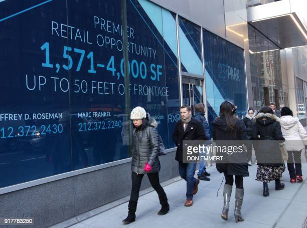 Pedestrians walk by a building advertising available retail space on Lexington Avenue on February 8 2018 in New York The New York borough of...