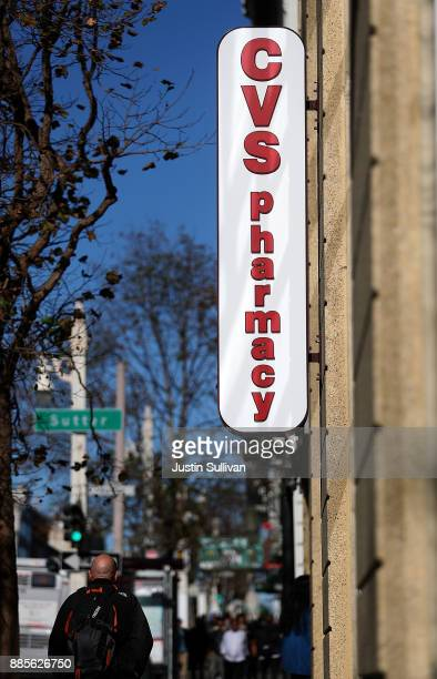 Pedestrians walk by a CVS Pharmacy on December 4 2017 in San Francisco California Drugstore chain CVS Health Corp announced plans on Sunday to...