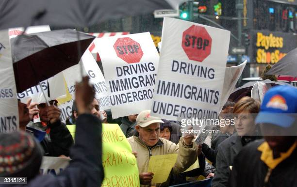 Pedestrians walk by a demonstration by immigrants and community leaders protesting the New York State Department of Motor Vehicles policies that deny...