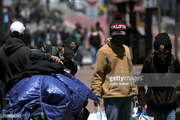 Pedestrians walk by a homeless man as he arranges his belongings on a cart on May 17 2019 in San Francisco California Results of a twoyear...