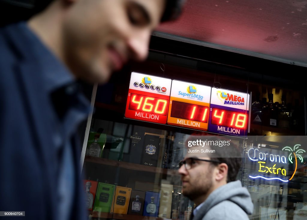 Pedestrians walk by a lottery sign at a convenience store on January 3, 2018 in San Francisco, California. The Powerball jackpot and Mega Millions jackpots are both over $400 million at the same time for the first time. The Mega Millions $418 million jackpot would be the fourth largest and the $460 million Powerball jackpot would be the seventh largest in the game's history.