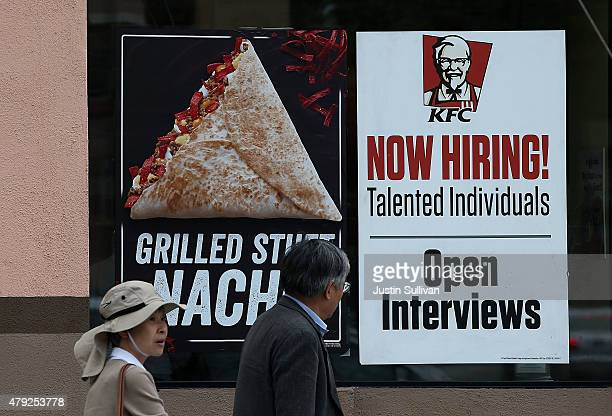 Pedestrians walk by a 'now hiring' sign at a KFC restaurant on July 2 2015 in San Francisco California According to a report by the US Labor...