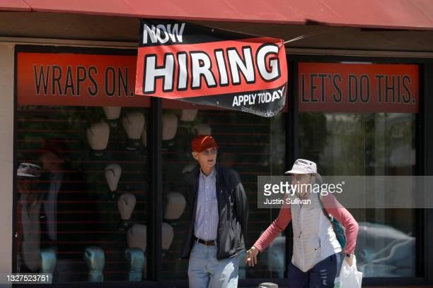 """Pedestrians walk by a """"Now Hiring"""" sign in front of a boxing gym on July 07, 2021 in San Rafael, California. As the economy continues to reopen..."""
