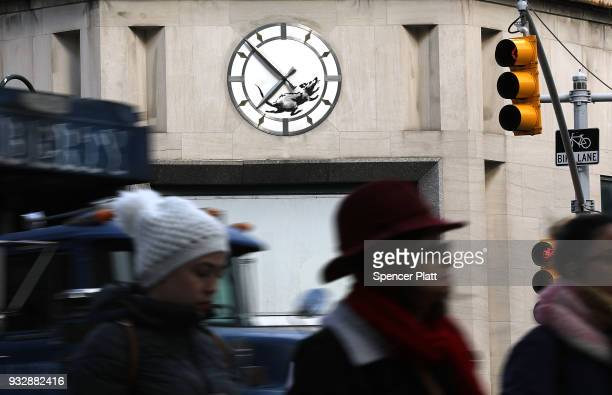 Pedestrians walk by a recent work by the elusive British street artist Bansky of a rat on the clock on the front of an old bank building at the...