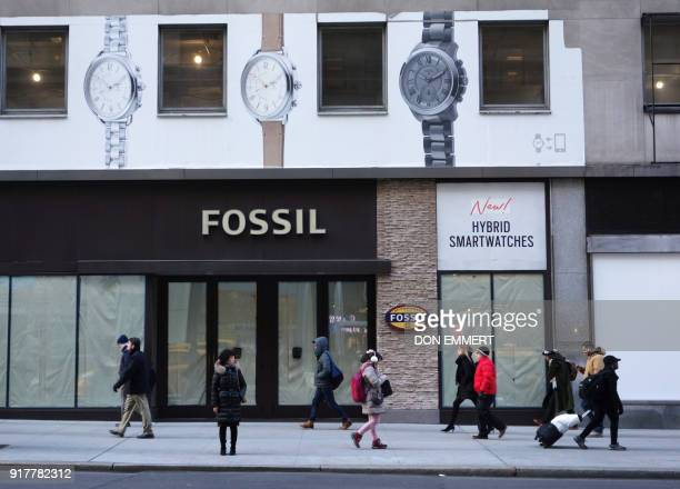 Pedestrians walk by a storefront with covered windows on 5th Ave on February 8 2018 in New York The New York borough of Manhattan is richer and more...