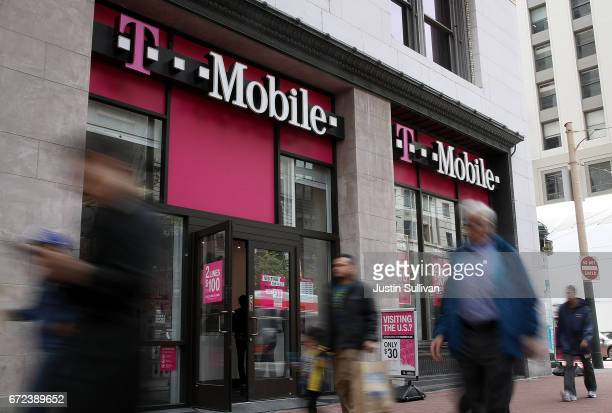 Pedestrians walk by a T-Mobile store on April 24, 2017 in San Francisco, California. T-Mobile will report first quarter earnings today after the...