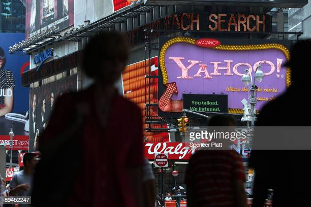 Pedestrians walk by a Yahoo sign in Times Square on July 29, 2009 in New York City. Taking aim at Google�s dominance, technology companies Microsoft...
