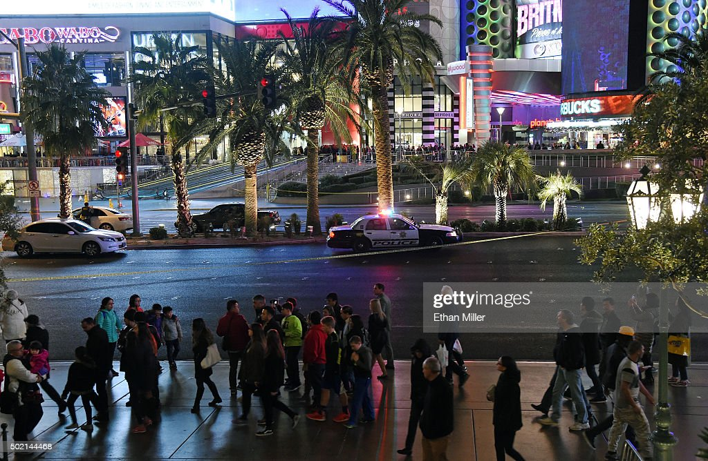 Pedestrians walk by across from Planet Hollywood Resort & Casino after police shut down all vehicle traffic on the Las Vegas Strip after a car crashed into a group of pedestrians on the sidewalk in front of the Paris Las Vegas and Planet Hollywood reportedly injuring 36 people and killing one on December 20, 2015 in Las Vegas, Nevada.