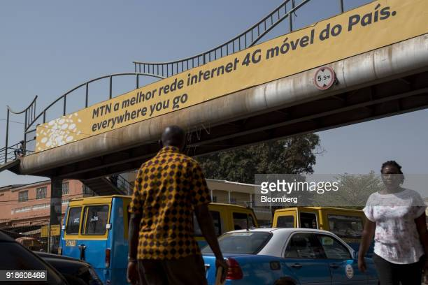Pedestrians walk by an MTN Group Ltd advertisement in Bissau GuineaBissau on Monday Feb 12 2018 The International Monetary Fund said an increase in...