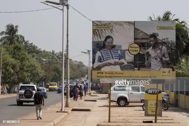 Pedestrians walk by an MTN Group Ltd advertisement in the Praa neighbourhood of Bissau GuineaBissau on Monday Feb 12 2018 The International Monetary...