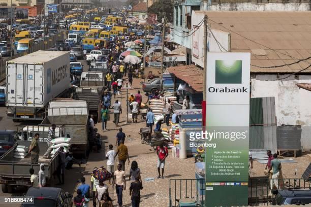 Pedestrians walk by an Orabank Guinea Bissau totem advertisement at Bandim market in Bissau GuineaBissau on Monday Feb 12 2018 The International...