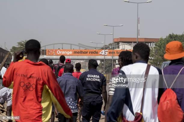 Pedestrians walk by an Orange Bissau SA advertisment in Bissau GuineaBissau on Monday Feb 12 2018 The International Monetary Fund said an increase in...