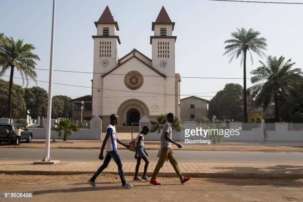 Pedestrians walk by Bissau Cathedral also known as Se Catedral de Nossa Senhora da Candelaria in Bissau GuineaBissau on Monday Feb 12 2018 The...