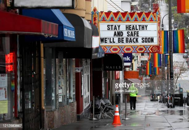 Pedestrians walk by the Castro Theatre that has a marquee announcing that they are closed due to a statewide ordinance banning gatherings of more...