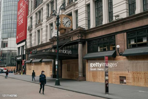 Pedestrians walk by the Macy's flagship store after workers cleaned and boarded up damage sustained during a night of violent protests and looting in...