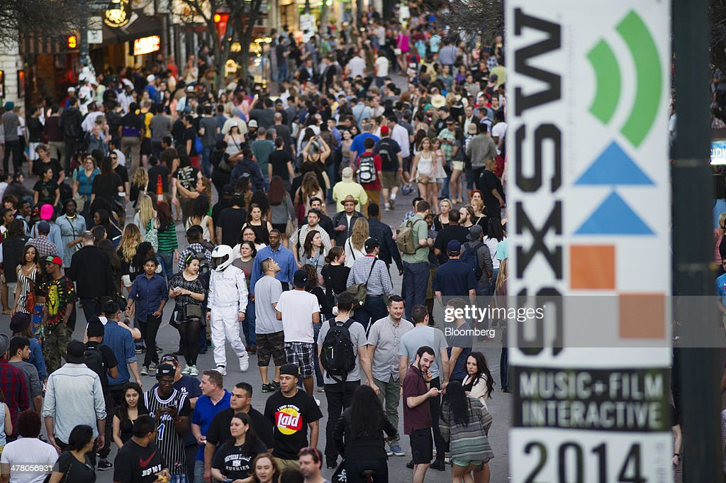 Pedestrians walk down 6th Street during the South By Southwest (SXSW) Interactive Festival in Austin, Texas, U.S., on Tuesday, March 11, 2014. The SXSW conferences and festivals converge original music, independent films, and emerging technologies while fostering creative and professional growth. Photographer: David Paul Morris/Bloomberg via Getty Images