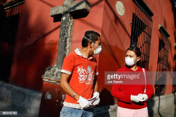 Pedestrians walk down a street wearing surgical masks to help prevent contamination with the swine flu May 2 2009 in Mexico City Mexico The Mexican...