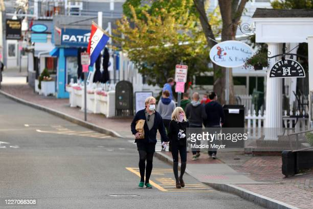 Pedestrians walk down Commercial Street on May 25, 2020 in Provincetown, Massachusetts. Massachusetts has begun Phase 1 of reopening after the...