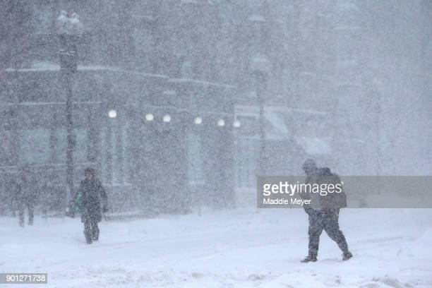 Pedestrians walk down Massachusetts Avenue during a massive winter storm on January 4 2018 in Boston Massachusetts Schools and businesses throughout...